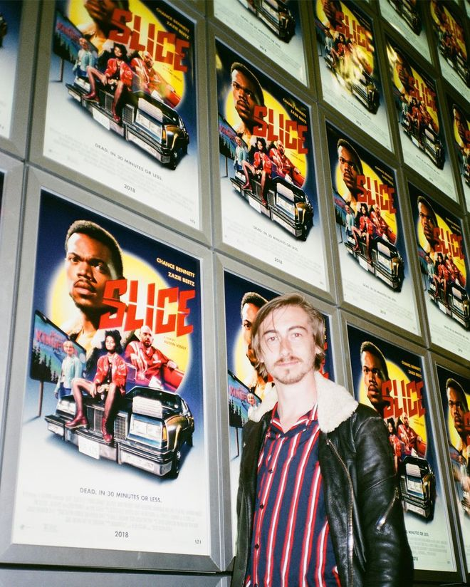 IMAGE: Austin Vesely in front of posters at the premiere of Slice posters